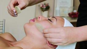 Massaggio facciale con le fette di pietre per la giovane donna nel salone della stazione termale di bellezza video d archivio