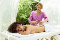 Massaggio tailandese della palla Donna nella STAZIONE TERMALE di giorno che ottiene massaggio di erbe tailandese della compressa Fotografia Stock