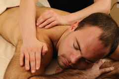 Massaging Back and Shoulders fo Man at Day Spa. Young receiving a full body massage at day spa Stock Image
