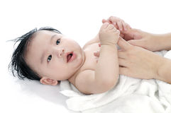 Massaging Cute Infant Baby. Portrait of a cute infant baby lying on back, over white background Stock Photography