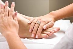 Massaging feet Stock Photography