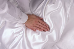 Massaging hands. With white sleeves on white silk Stock Photo