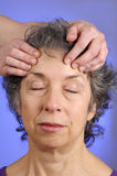 Massaging Head of Senior Woman Royalty Free Stock Images