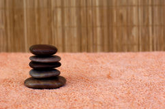 Massaging stones 1. Hot massaging stones in a spa on a towel with a bamboo mattress as background royalty free stock photo