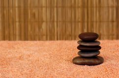 Massaging stones 2. Hot massaging stones in a spa on a towel with a bamboo mattress as background stock image