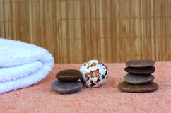 Massaging stones 6. Hot massaging stones and bath pearls in a spa on a towel with a bamboo mattress as background royalty free stock photo
