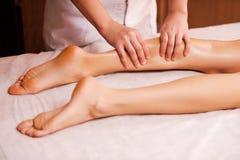 Massaging tired legs. Close-up of massage therapist massaging beautiful female leg Royalty Free Stock Photos