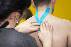 Massaging of young man - kinesiotaping. Massaging of young man in SPA Royalty Free Stock Image