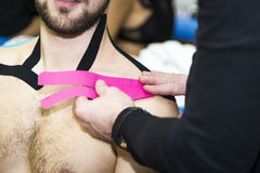 Massaging of young man - kinesiotaping. Massaging of young man in SPA Stock Images