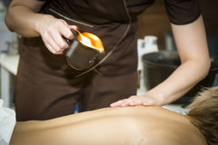 Massaging of young woman with paraffin wax. Massaging of young woman in SPA Stock Photo