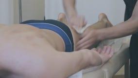 Massagist die beenmassage voor de mens in de kliniek maken stock video