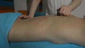 Massagist die hete stenen gebruiken stock footage