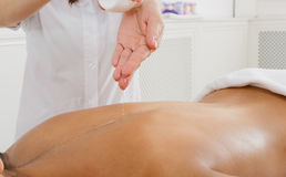 Massagist make oil body massage in spa wellness center. Closeup of oil pouring on unrecognizable woman's back for massage in spa wellness center. Professional Royalty Free Stock Images