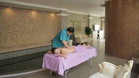 Massagist masculino que hace el masaje trasero de la mujer en salón del balneario metrajes