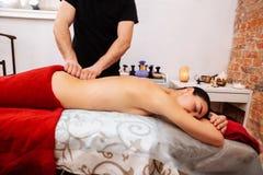 Massagista apto forte na rotação de trituração uniforme preta da mulher de encontro imagem de stock royalty free