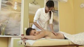 Massagista de sorriso que faz a massagem no corpo da jovem mulher em um salão de beleza dos termas video estoque