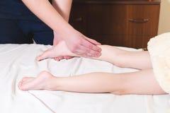 Massagista masculino do fisioterapeuta do close-up que faz uma massagem de relaxamento cura do pé a uma criança pequena que encon foto de stock