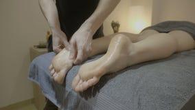Massagista masculino novo profissional que fricciona os pés de seu cliente com o óleo e que faz massagens os delicadamente em um  video estoque