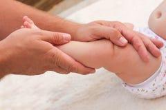 Massagista que faz a massagem para o bebê pequeno do pé Fotografia de Stock