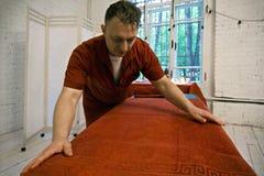 Massagista que prepara o sofá da massagem Fotos de Stock Royalty Free