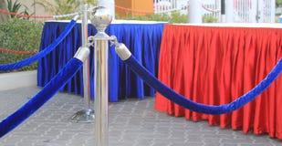 Massenkontrollesperren mit den blauen Samtfessel- und Aufnahmetabellen bedeckt mit roter und blauer silk Franse Lizenzfreies Stockfoto