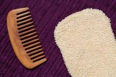 Massera handsken och trähårhårkammen på den purpurfärgade badlakanet arkivfoto