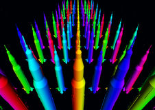 Masses of colorful rockets. Computer generated 3D illustration with masses of colorful rockets against a black background Royalty Free Stock Images