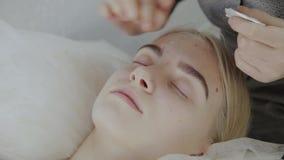 Masseur прикладывает лицевую сливк массажа к маленькой девочке в салоне красоты акции видеоматериалы