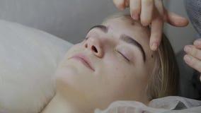 Masseur прикладывает лицевую сливк массажа к маленькой девочке в салоне красоты сток-видео
