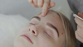 Masseur прикладывает лицевую сливк массажа к маленькой девочке в салоне красоты видеоматериал