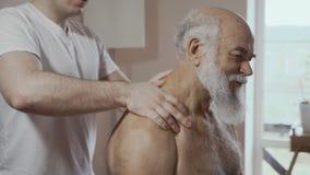 Masseur делает терапевтический массаж к старшему человеку сток-видео
