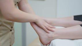 Masseur делает терапевтический массаж ноги к девушке Конец-вверх видеоматериал