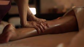 Masseur делая массаж ног с маслом к молодой женщине в салоне спа курорта Молодая женщина получая массаж тела в роскошном спа акции видеоматериалы