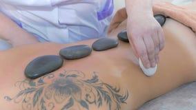 Masseur делая расслабляющий массаж с камнем сток-видео
