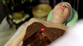 Masseur кладет теплый шоколад на тело ` s девушки для массажа сток-видео