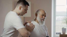 Masseur массажирует плечо пожилого человека акции видеоматериалы
