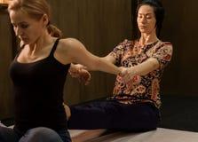 Masseur массажируя назад женщины в спа-курорте, расслабленный пациент наслаждается Тайский массаж или тайская обработка массажа й Стоковые Изображения