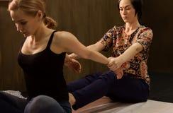 Masseur массажируя назад женщины в спа-курорте, расслабленный пациент наслаждается Тайский массаж или тайская обработка массажа й Стоковое Изображение
