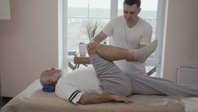 Masseur нагревает колено старшего человека видеоматериал
