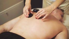 Masseur ослабляет массаж с горячими камнями для человека сток-видео