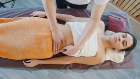Masseur подготавливая молодую женщину для расслабляющего массажа живота со штриховать движения видеоматериал