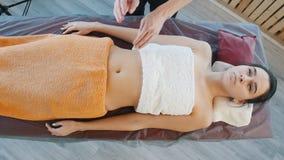 Masseur подготавливая молодую женщину для расслабляющего массажа живота с tweaking движениями видеоматериал