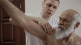 Masseur проверяет эффективность руки старика сток-видео
