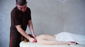 Masseur с сильными руками замешивает шею молодой женщины которая лежит на кресле в светлой комнате косметологии акции видеоматериалы