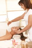Masseur applying cream on face. Masseur applying cream on young woman's face in spa stock photos