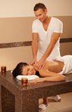 Masseur and client. Masseur doing massage for client on massage table, relaxing treatment Stock Images