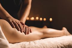 A masseur in a dark room does a hip massage with oil for a woman. Spa procedures massage women.  stock photos