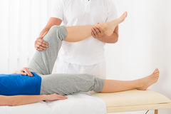 Masseur, der der Frau Bein-Massage gibt Lizenzfreies Stockbild