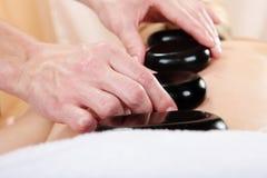 Masseur die massage maakt door hete stenen in kuuroord Royalty-vrije Stock Foto's