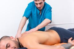 Masseur doing a back massage on a client Royalty Free Stock Photos